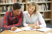 student with tutor in library