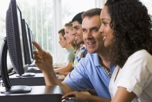students on computers with a teacher helping one of the students