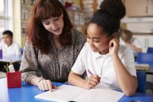 teacher reviewing work with a student at her desk