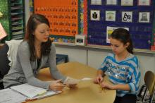 Student discussing text with teacher.