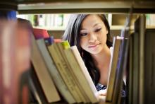 student in library looking at books